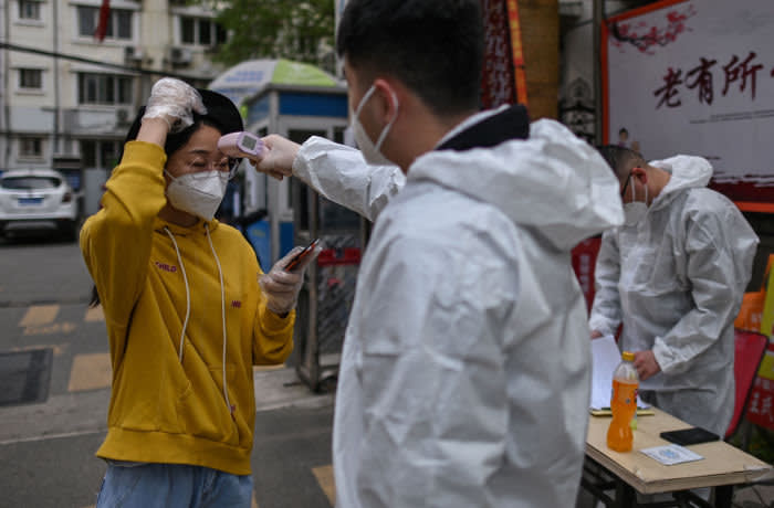 A man wearing a protective suit checks a woman's temperature next to a residential area in Wuhan, in China's central Hubei province on April 7, 2020. - Wuhan, the central Chinese city where the coronavirus first emerged last year, partly reopened on March 28 after more than two months of near total isolation for its population of 11 million. (Photo by Hector RETAMAL / AFP) (Photo by HECTOR RETAMAL/AFP via Getty Images)