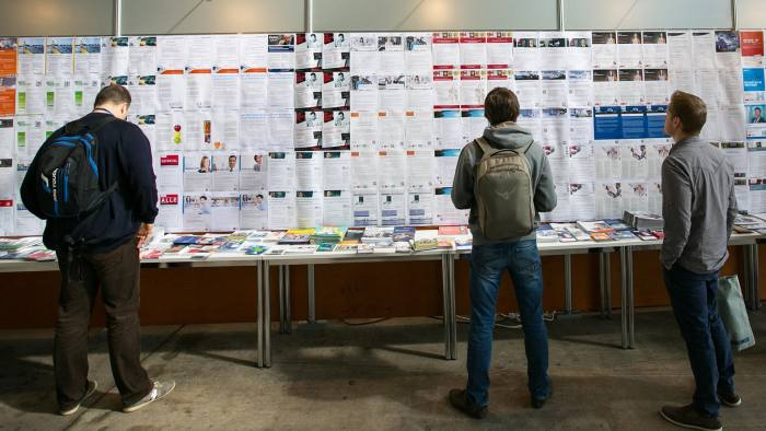 Bloomberg Photo Service 'Best of the Week': Visitors look at employment opportunities displayed on a job board at the Connecticum job fair for students, graduates and young professionals at Tempelhof airport in Berlin, Germany, on Tuesday, May 6, 2014. German unemployment fell more than twice as much as forecast in April in a sign that Europe's largest economy will continue to lead the recovery in the euro area. Photographer: Krisztian Bocsi/Bloomberg