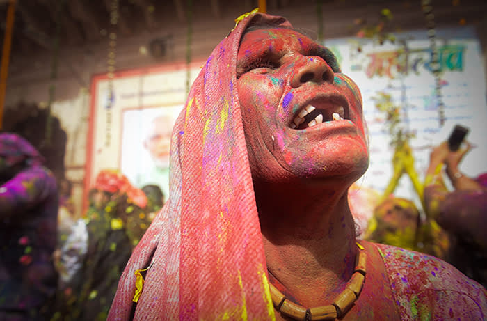 TOPSHOT - An Indian widow gestures covered in coloured powder while dancing during Holi festival or festival of colours celebrations in Vrindavan on February 27, 2018. Holi, the popular Hindu spring festival of colours is observed in India at the end of the winter season on the last full moon of the lunar month, and will be celebrated on March 1 this year. / AFP PHOTO / Noemi CASSANELLINOEMI CASSANELLI/AFP/Getty Images