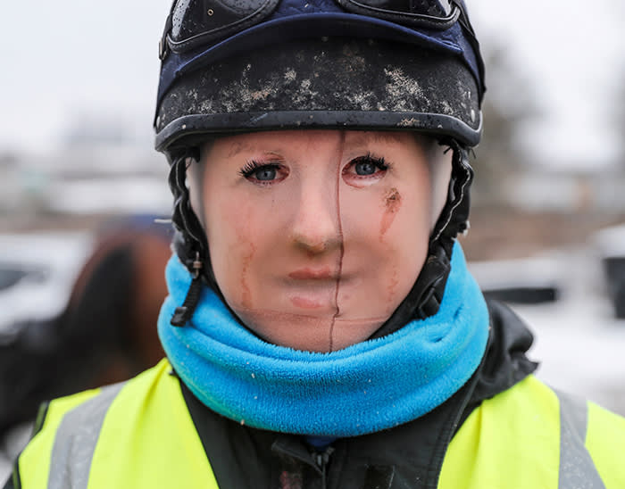 Trainer Lawney Hill poses for a photograph as she wears tights over her face to keep out the cold after taking her horses out on the all-weather gallops in Tetsworth, Britain, March 2, 2018. REUTERS/Eddie Keogh TPX IMAGES OF THE DAY