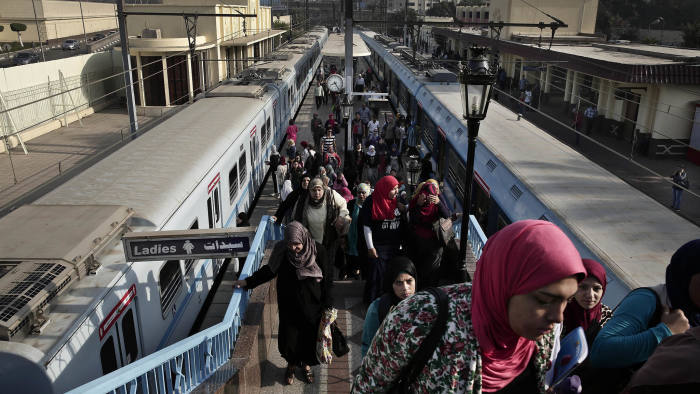 In this Thursday, Oct. 27, 2016 photo, Egyptian women exit a metro station in Cairo, Egypt. On Thursday, Nov. 3, 2016, Egypt devalued its currency by 48 percent, meeting a key demand set by the International Monetary Fund in exchange for a $12 billion loan over three years to overhaul the country's ailing economy. The much heralded decision by the Egyptian Central Bank to devalue the pound followed a sharp and sudden decline this week in the value of the dollar in the unofficial market, plunging from an all-time high of 18.25 pounds to around 13 to the U.S. currency. (AP Photo/Nariman El-Mofty)