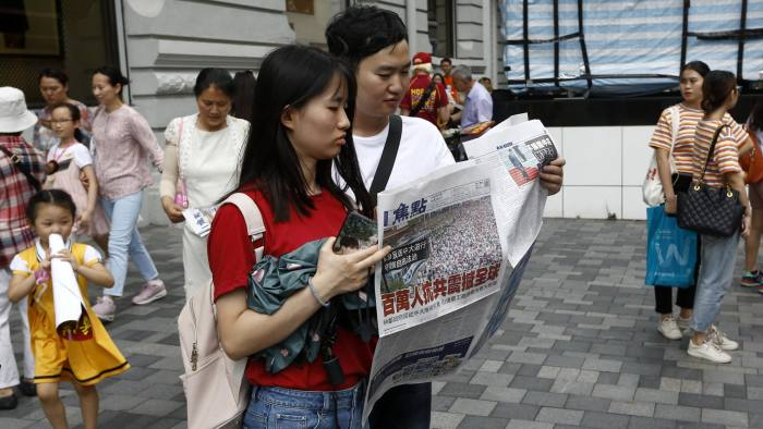 """A man and a woman reads a newspaper with the headlines """"Millions against Communist China shock the world"""" distributed in a shopping district popular with mainland Chinese tourists in Hong Kong Sunday, July 7, 2019. A march was to go through a popular shopping area for Chinese tourists and end at a high-speed rail station that connects the city to the mainland. (AP Photo/Andy Wong)"""