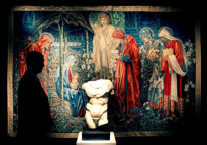 A Christie's employee stands in front of a 1904 tapestry by Sir Edward Coley Burne-Jones and a 1st-2nd century marble torso on January 29, 2009 in London. The private collection of Yves Saint Laurent and Pierre Berge is on show in London and will be sold at auction in Paris from 23rd to 25th February 2009.