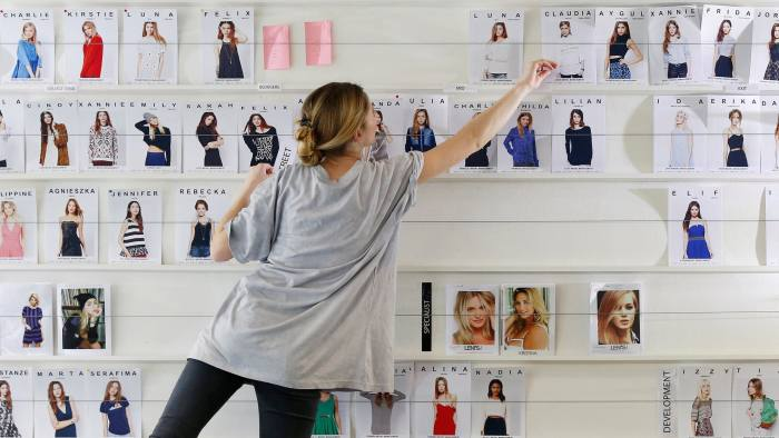 FILE PHOTO: An employee organises photographs of models at the ASOS headquarters in London April 1, 2014. REUTERS/Suzanne Plunkett/File Photo