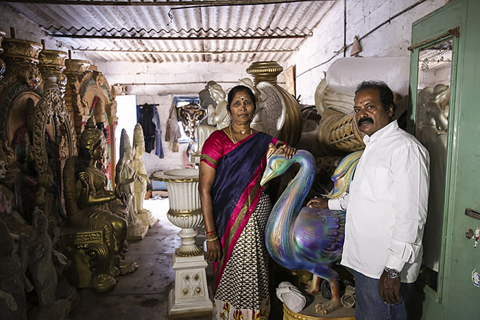 Indira and Sunder Raj pose for a photograph in their idol making workshop in Bangalore, India. Indira supports her family business regularly borrowing from Ujjivan to procure raw material.