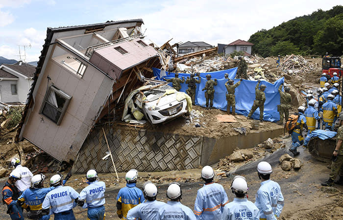 Rescue workers look for missing people in a house damaged by heavy rain in Kumano town, Hiroshima Prefecture, Japan, in this photo taken by Kyodo July 9, 2018. Mandatory credit Kyodo/via REUTERS ATTENTION EDITORS - THIS IMAGE WAS PROVIDED BY A THIRD PARTY. MANDATORY CREDIT. JAPAN OUT. NO COMMERCIAL OR EDITORIAL SALES IN JAPAN. TPX IMAGES OF THE DAY