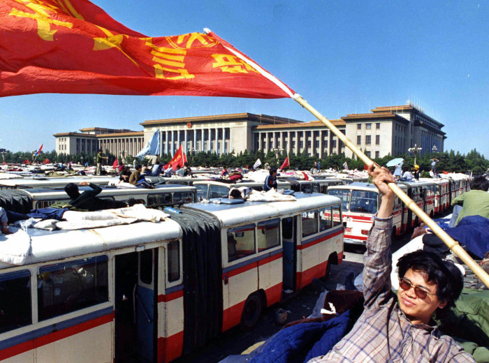 A Beijing university student waves a flag from the top of a bus parked in Tiananmen Square, Beijing, May 23, 1989, during the students strike for democracy. In the background is the Great Hall of the People. (AP Photo/Shing)