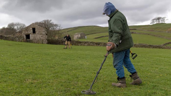 RA40MJ Metal detectors searching farmland in Wensleydale for metal artefacts. North Yorkshire, UK.