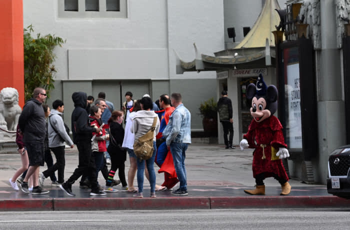 An actor in a Mickey Mouse costume looks for tourists who want to take photos with them in exchange for tips, in front of the TCL Chinese Theatre March 15, 2020 in Hollywood, California. - The spread of novel coronavirus COVID-19 has negatively affected a wide range of industries all across the global economy. (Photo by Robyn Beck / AFP) (Photo by ROBYN BECK/AFP via Getty Images)