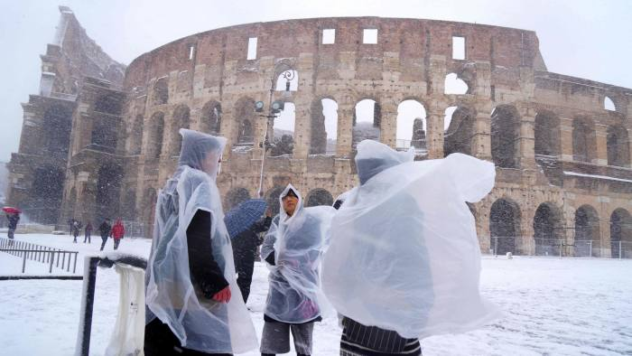 TOPSHOT - Japanese tourists put plastic coats as they visit the ancient Colosseum during a snowfall in Rome on February 26, 2018.     / AFP PHOTO / Vincenzo PINTOVINCENZO PINTO/AFP/Getty Images