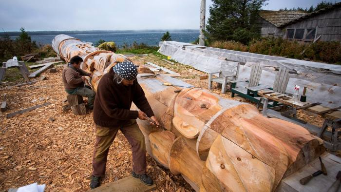 A First Nations artists work on a totem pole in the village of Old Massett, British Columbia, Canada, on Thursday, Aug. 25, 2016. Facing five major energy initiatives in B.C., Canadian Prime Minister Trudeau will choose which constituency to abandon. He's allowed a hydroelectric dam to proceed; pending are decisions on Enbridge Inc.'s Northern Gateway crude pipeline, Petroliam Nasional Bhd.'s LNG project on Lelu Island, a pipeline expansion by Kinder Morgan Inc., as well as a ban on crude oil tankers. Photographer: Ben Nelms/Bloomberg