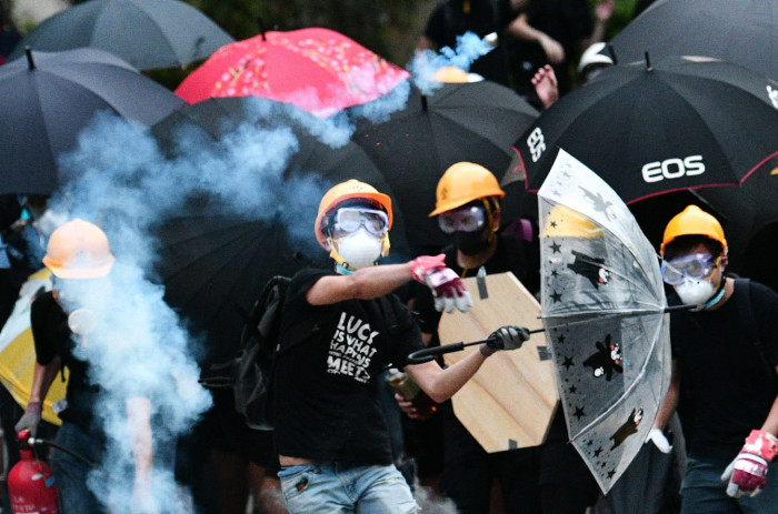 TOPSHOT - A protester throws back a round of tear gas fired by the police during a demonstration in the district of Yuen Long in Hong Kong on July 27, 2019. - Hong Kong police fired tear gas and rubber bullets on July 27 at protesters holding a banned rally against suspected triad gangs who beat up pro-democracy demonstrators near the Chinese border last weekend, tipping the finance hub further into chaos. (Photo by Anthony WALLACE / AFP)ANTHONY WALLACE/AFP/Getty Images