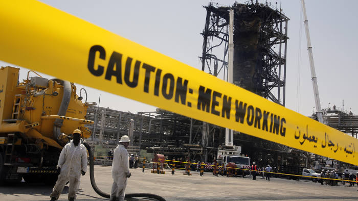 In this photo opportunity during a trip organized by Saudi information ministry, workers work in front of the recent attack Aramco's oil processing facility in Khurais, near Dammam in the Kingdom's Eastern Province, Friday, Sept. 20, 2019. (AP Photo/Amr Nabil)