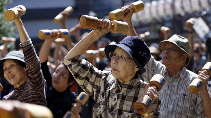 """Elderly and middle-age people exercise with wooden dumbbells during a health promotion event to mark Japan's """"Respect for the Aged Day"""" at a temple in Tokyo...Elderly and middle-age people exercise with wooden dumbbells during a health promotion event to mark Japan's """"Respect for the Aged Day"""" at a temple in Tokyo's Sugamo district, an area popular among the Japanese elderly, September 21, 2015. REUTERS/Issei Kato - RTS2362"""
