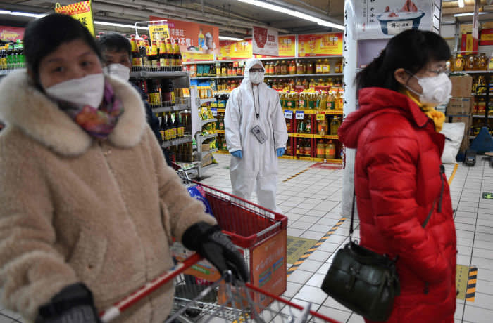 TOPSHOT - A worker wears protective clothing as a preventive measure against the COVID-19 coronavirus as she watches over customers in a supermarket in Beijing on March 3, 2020. The world has entered uncharted territory in its battle against the deadly coronavirus, the UN health agency warned, as new infections dropped dramatically in China on March 3 but surged abroad with the US death toll rising to six. - The world has entered uncharted territory in its battle against the deadly coronavirus, the UN health agency warned, as new infections dropped dramatically in China on March 3 but surged abroad with the US death toll rising to six. (Photo by GREG BAKER / AFP) (Photo by GREG BAKER/AFP via Getty Images)