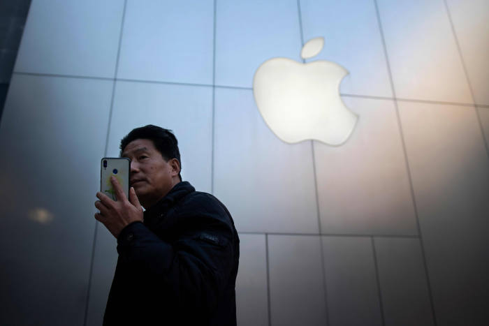 A man uses a smartphone outside an Apple store in Beijing on January 4, 2019. - Apple cut its revenue outlook for the latest quarter on January 3, citing steeper-than-expected
