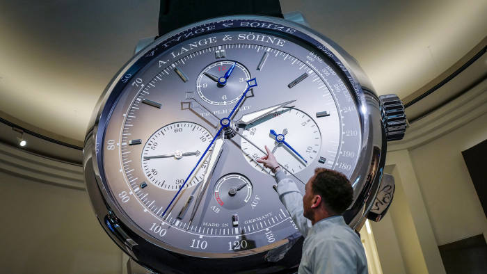 A staff gestures next to a giant watch at the stand of German watchmaker A. Lange
