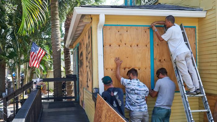 Employees of the Island Root Kava Lounge board up the windows of the business in preparation for Hurricane Dorian in Melbourne, Florida, U.S., on Sunday, Sept. 1, 2019. Dorian came ashore in the Bahamas tied as the most powerful storm to hit land anywhere in the Atlantic. The fate of Florida remains uncertain as the storm churns in the ocean. Photographer: Zack Wittman/Bloomberg