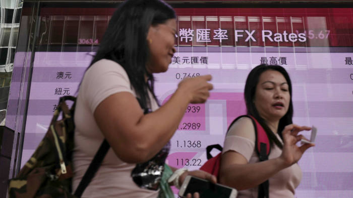 People walk past an electronic board showing the Hong Kong Stock Exchange index, Tuesday, July 4, 2017, in Hong Kong, China. Australian shares jumped Tuesday as investors awaited an interest rate decision by the central bank, while other Asian shares were mixed Tuesday ahead of a U.S. trading holiday. (AP Photo/Vincent Yu)