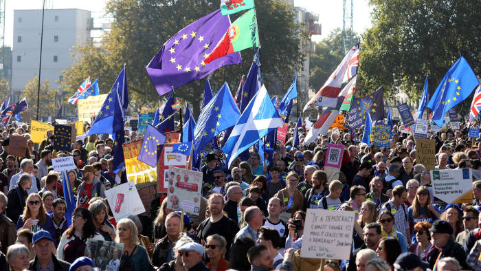 Demonstrators hold flags and placards as they march during the anti-Brexit People's Vote march, in London, U.K., on Saturday, Oct. 20, 2018. U.K. Prime Minister Theresa May is said to be ready to ditch one of her key Brexit demands in order to resolve the vexed issue of the Irish border and clear the path to a deal, according to people familiar with the matter. Photographer: Chris Ratcliffe/Bloomberg
