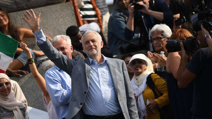 LONDON, ENGLAND - JULY 13: Labour Party leader Jeremy Corbyn waves as he visits Trafalgar Square at a demonstration against President Trump's visit to the UK on July 13, 2018 in London, England. Tens of Thousands Of Anti-Trump protesters are expected to demonstrate in London and across the country against the UK visit by the President of the United States. Many people disagree with his policies that include migrant family separation, discrimination of transgender military personnel and changes to laws protecting women's sexual health. (Photo by Chris J Ratcliffe/Getty Images)