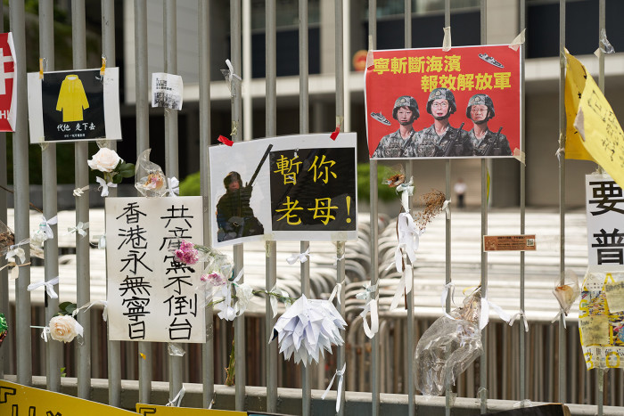 Posters, ribbons and flowers left by protesters adorn a barrier in central Hong Kong