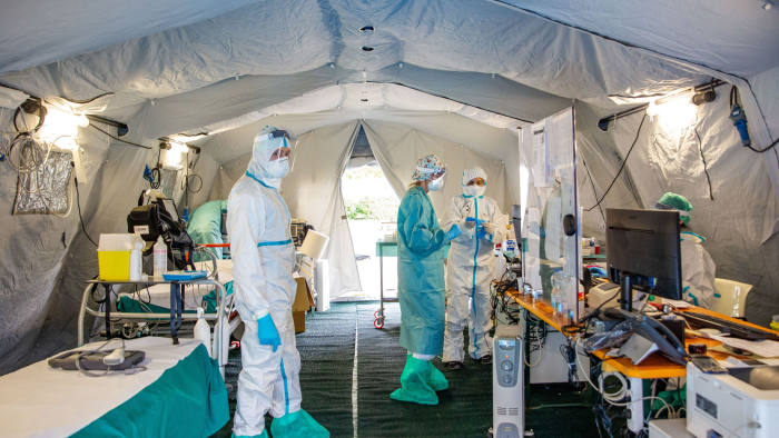 Medical personnel work inside a triage tent at a hospital in Brescia, Italy, on Friday, March 13, 2020. Europe's largest coronavirus outbreak is putting unprecedented strain on the Italian health-care system, with hospitals in the worst-affected areas close to the breaking point. Photographer: Francesca Volpi/Bloomberg