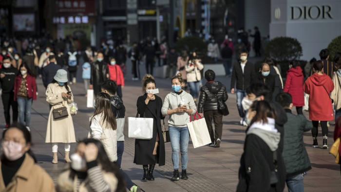Shoppers and pedestrians wearing protective masks walk past stores on Nanjing Road in Shanghai, China, on Saturday, March 14, 2020. Data on China's industrial output, investment and retail sales due Monday are forecast to show an across-the-board contraction for the first time on record, evidence of the extent to which the coronavirus has ravaged the economy. Photographer: Qilai Shen/Bloomberg