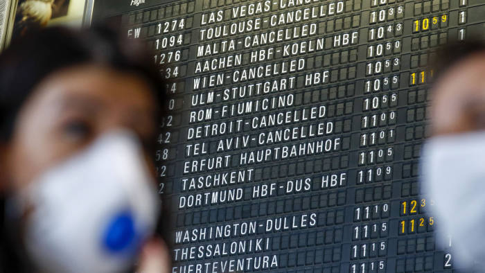 Travelers wear face masks near a flight departure information board showing some cancelled flights at Frankfurt Airport, operated by Fraport AG, in Frankfurt, Germany, on Thursday, March 12, 2020. President Donald Trump's 30-day ban on Europeans traveling to the U.S. delivers a hammer blow to a global airline industry that was already at risk of losing as much as $113 billion in passenger revenue this year because of the coronavirus. Photographer: Alex Kraus/Bloomberg