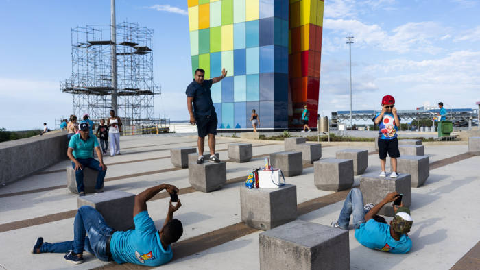 Visitors take advantage of a photo opportunity at La Ventana al mundo, a new piece of public art in Barranquilla