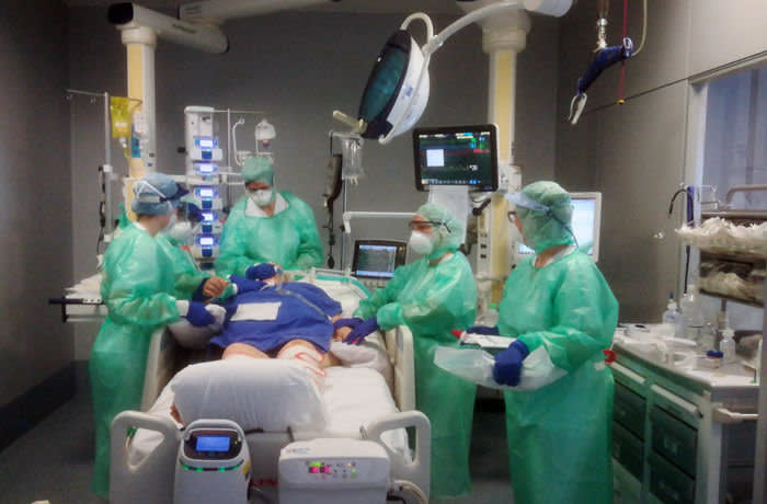Medical staff assist a patient in the Intensive Care Unit of the Bergamo Papa Giovanni XXIII hospital, Italy, Tuesday, March 17, 2020. For most people, the new coronavirus causes only mild or moderate symptoms. For some it can cause more severe illness, especially in older adults and people with existing health problems.(ASST Papa Giovanni XXIII via AP)
