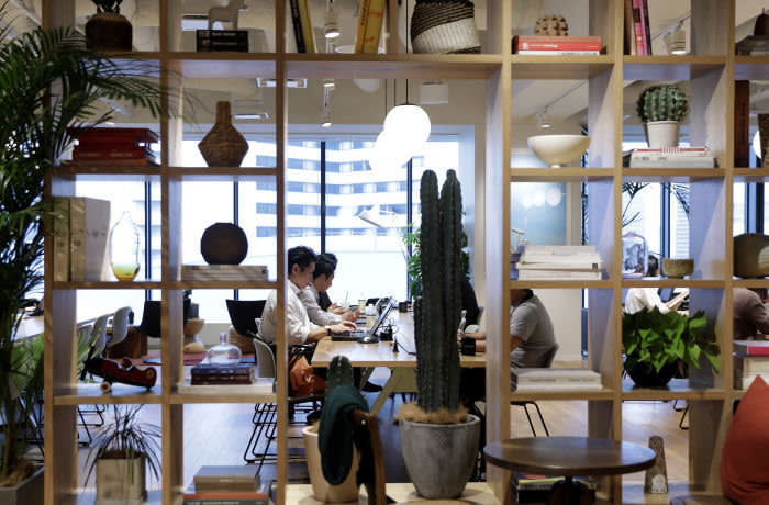 Members sit around a communal working table inside the WeWork Ocean Gate Minatomirai co-working office space, operated by The We Company, in Yokohama, Japan, on Friday, Oct. 11, 2019. WeWork formally withdrew the prospectus for an IPO this month, capping a botched fundraising effort that cost its top executive his job. The defeat places urgency on WeWork to find new sources of capital to keep its business running Photographer: Kiyoshi Ota/Bloomberg