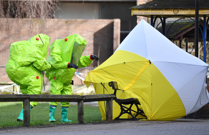 """Members of the emergency services in green biohazard suits afix the tent over the bench where a man and a woman were found on March 4 in critical condition at The Maltings shopping centre in Salisbury, southern England, on March 8, 2018 after the tent became detached. British detectives on March 8 scrambled to find the source of the nerve agent used in the """"brazen and reckless"""" attempted murder of a Russian former double-agent and his daughter. Sergei Skripal, 66, who moved to Britain in a 2010 spy swap, is unconscious in a critical but stable condition in hospital along with his daughter Yulia after they collapsed on a bench outside a shopping centre on Sunday. / AFP PHOTO / Ben STANSALLBEN STANSALL/AFP/Getty Images"""