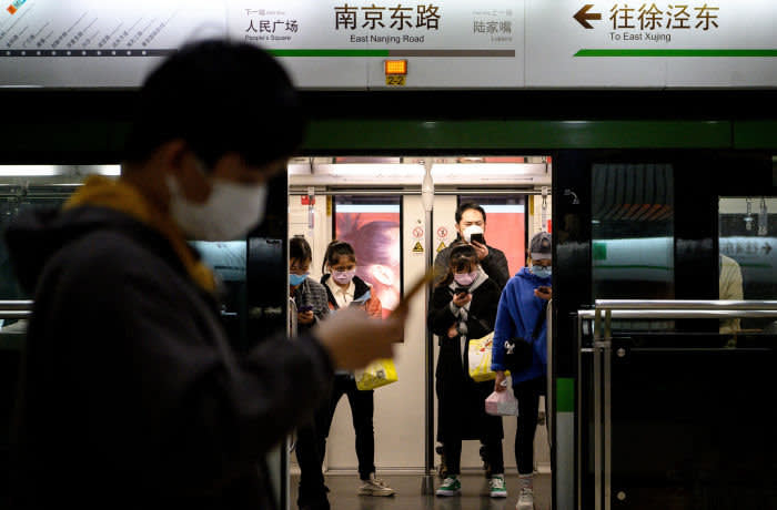 TOPSHOT - People wearing protective facemasks use their mobile phones on the subway in Shanghai on February 25, 2020. - The new coronavirus has peaked in China but could still grow into a pandemic, the World Health Organization warned, as infections mushroom in other countries. (Photo by NOEL CELIS / AFP) (Photo by NOEL CELIS/AFP via Getty Images)