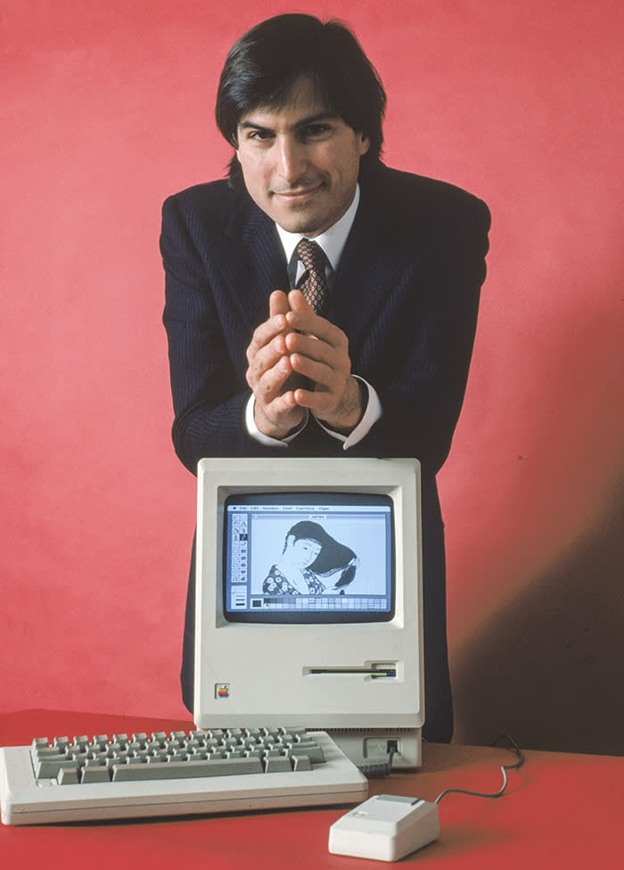 American computer magnate and co-founder of Apple Computer Steve Jobs leans on the his Macintosh 128K, the original Macintosh personal computer, featuring MacPaint, circa 1984. (Photo by Bernard Gotfryd/Getty Images)