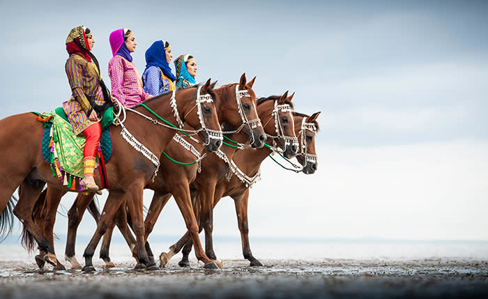 Embargoed to 0001 Thursday August 16, 2018. Women from the Oman Royal Cavalry's Combined Bands who are performing at The Royal Edinburgh Military Tattoo wear their traditional Arabian dress as they exercise their animals on the city's Portobello beach. PRESS ASSOCIATION Photo. Picture date: Tuesday August 14, 2018. Members of the Oman Royal CavalryÕs Mounted Pipes and Drums and all-female marching Band, and 23 Arabian purebred horses which belong to the Sultan of Oman, have travelled 5,000 miles from Muscat to join 1,200 international performers to participate in its ÔSkyÕs the LimitÕ showcase and the Tatoo's 69th show. See PA story ARTS Tattoo. Photo credit should read: Royal Edinburgh Military Tattoo/PA Wire NOTE TO EDITORS: This handout photo may only be used in for editorial reporting purposes for the contemporaneous illustration of events, things or the people in the image or facts mentioned in the caption. Reuse of the picture may require further permission from the copyright holder.