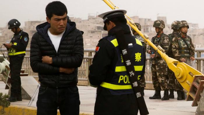 """A police officer checks the identity card of a man as security forces keep watch in a street in Kashgar, Xinjiang Uighur Autonomous Region, China, March 24, 2017. REUTERS/Thomas Peter SEARCH """"XINJIANG PETER"""" FOR THIS STORY. SEARCH """"WIDER IMAGE"""" FOR ALL STORIES."""