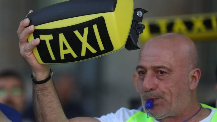A protestor holds up a taxi cab roof sign during a demonstration against Uber Technologies Inc. outside the Noah Technology Conference in Berlin, Germany, on Wednesday, June 6, 2018. The conference, one of the tech industry's premier events, was launched in 2009 and runs June 6-7. Photographer: Krisztian Bocsi/Bloomberg