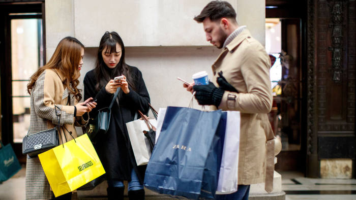 Shoppers carry purchases as they look at their smartphones on the main shopping district on Oxford Street in London on December 13, 2018 less than two weeks before Christmas. (Photo by Tolga Akmen / AFP) (Photo credit should read TOLGA AKMEN/AFP/Getty Images)