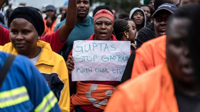 Employees and contractors of the Optimum Coal Mine in Hendrina, owned by the controversial Gupta family, demonstrate with a placard reading 'Guptas - stop gambling with our lives' in front of the gates of the mine in Hendrina, South Africa, on February 22, 2018. Workers are on strike because of the Bank of Baroda withdrawing Services in South Africa and reduced the operations to a standstill as they marched to hand over a memorandum to the company's CEO. / AFP PHOTO / MARCO LONGARI (Photo credit should read MARCO LONGARI/AFP/Getty Images)