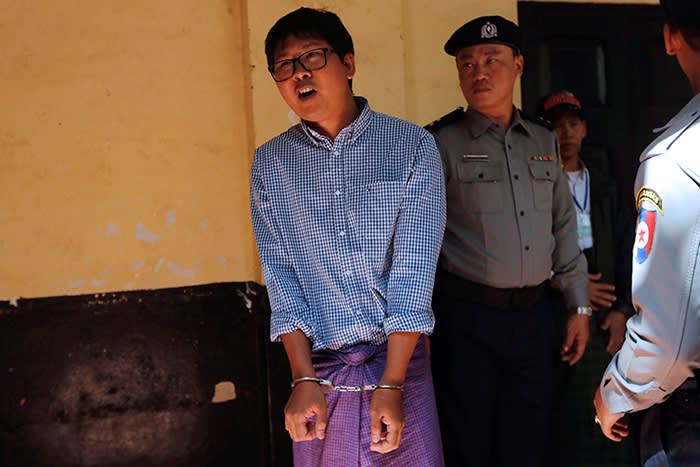 Detained Reuters journalist Wa Lone is escorted by police during a break at a court hearing in Yangon, Myanmar February 1, 2018. REUTERS/Jorge Silva - RC14BC2A3C70