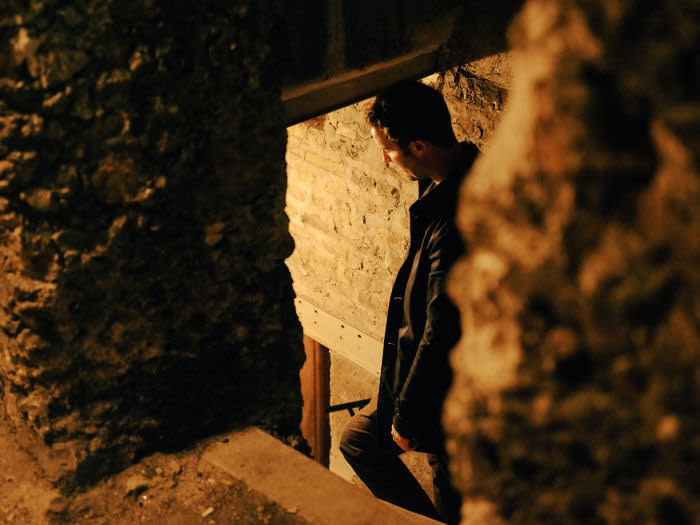 David Keohane descends into the basement of his building, where a squatter had been living