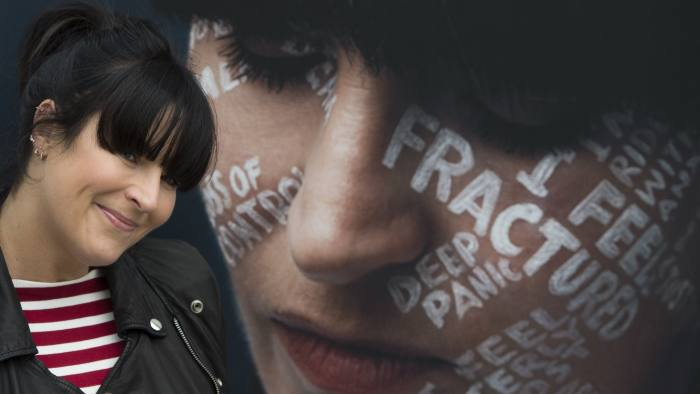 Anna Richardson stands next to a portrait of herself at an outdoor exhibition in RegentÕs Place in London, during the launch of the LetÕs Talk campaign, to encourage people to talk about mental health. PRESS ASSOCIATION Photo. Picture date: Monday October 8, 2018. By drawing peopleÕs most difficult thoughts on their faces, photographer Charlie Clift and lettering artist Kate Forrester hope to inspire others to open up about their own mental health. See PA story HEALTH Riley. Photo credit should read: David Mirzoeff/PA Wire