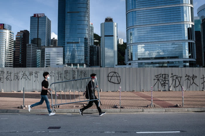 ADMIRALTY, HONG KONG, HONG KONG SAR, CHINA - 2019/07/01: Protesters carrying metal barrier in front of a graffiti wall and skyscrapers in the surroundings of Hong Kong Legislative Council during protests against extradition law to China. (Photo by Ivan Abreu/SOPA Images/LightRocket via Getty Images)