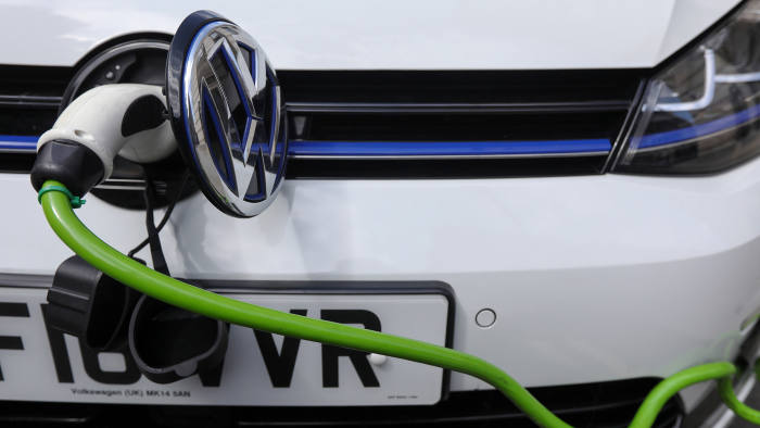 A charging plug sits next to a VW badge cover in the port of a Volkswagen AG GTE Golf hybrid automobile at a charging station in London U.K., on Thursday, Aug. 10, 2017. The U.K. government plans to invest more than 800 million pounds ($1 billion) in new driverless and zero-emission vehicle technology as it seeks to boost its economy while leaving the European Union. Photographer: Luke MacGregor/Bloomberg