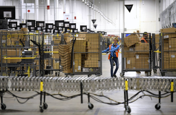 FILE - In this Friday, March 23, 2018, file photo, associates move bins filled with products at the loading dock of Amazon's then-new fulfillment center in Livonia, Mich. Amazon said Monday, March 16, 2020 that it needs to hire 100,000 people across the U.S. to keep up with a crush of orders as the coronavirus spreads and keeps more people at home, shopping online. (Todd McInturf/Detroit News via AP)