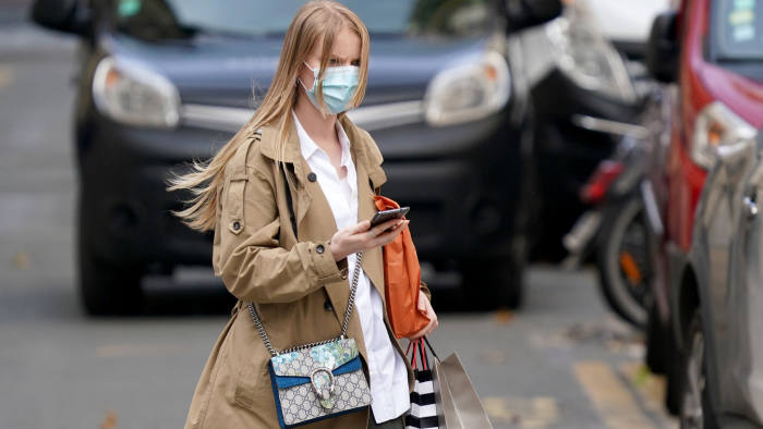 PARIS, FRANCE - MAY 11: A passerby wears a beige trench coat, a white shirt, a Gucci bag, sneakers, a face mask, in the streets of Paris, on May 11, 2020 in Paris, France. (Photo by Edward Berthelot/Getty Images)