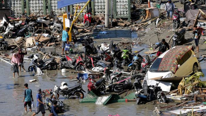 People survey damage outside the shopping mall following earthquakes and tsunami in Palu, Central Sulawesi, Indonesia, Sunday, Sept. 30, 2018. Rescuers try to reach trapped victims in collapsed buildings after hundreds of people are confirmed dead in a tsunami that hit two central Indonesian cities, sweeping away buildings with massive waves. (AP Photo/Tatan Syuflana)