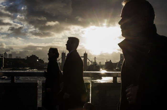 Stormy Weather To Hit The UK...LONDON, ENGLAND - OCTOBER 21: City workers walk over London Bridge as the early morning sun breaks through clouds on October 21, 2014 in London, England. Despite weather warnings issued by the Met Office for high winds and rain off the back of Hurricane Gonzalo, those predictions didn't materialise in London. (Photo by Dan Kitwood/Getty Images)
