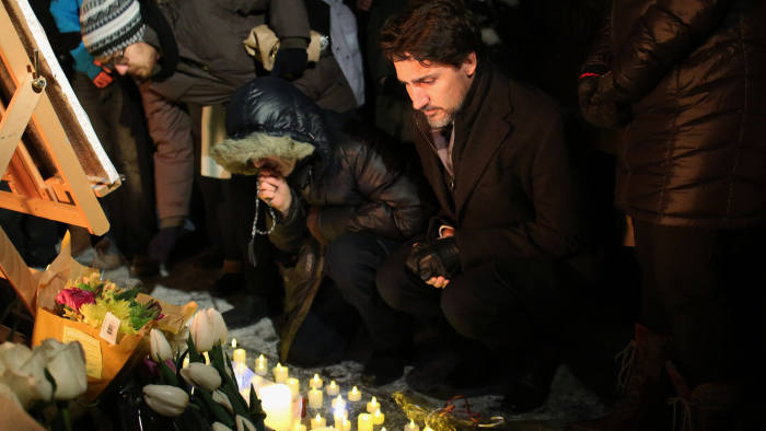 Justin Trudeau places a candle on Parliament Hill, Ottawa, during a vigil for victims killed in a plane crash in Iran